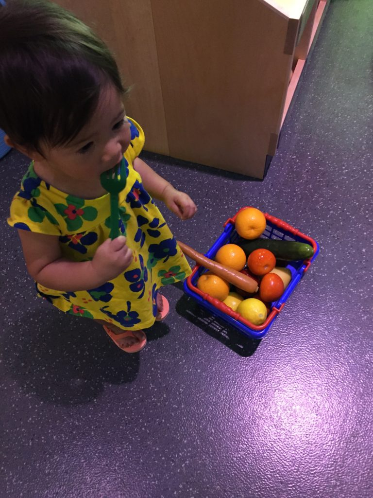 Ava gathering some fruit in a basket with the help of some new friends.